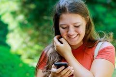 Gelukkig meisje die een slimme telefoon in de zomer in een park met behulp van die en camera glimlachen bekijken Stock Afbeelding