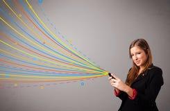 Gelukkig meisje die een telefoon met kleurrijke abstracte lijnen houden Royalty-vrije Stock Afbeeldingen