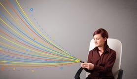 Gelukkig meisje die een telefoon met kleurrijke abstracte lijnen houden Stock Foto