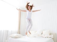 Gelukkig meisje die en pret in bed springen hebben Royalty-vrije Stock Fotografie