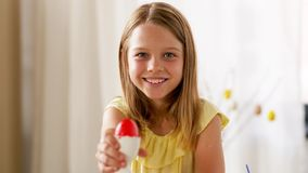 Gelukkig meisje die gekleurd paasei thuis tonen stock video