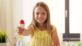 Gelukkig meisje die gekleurd paasei thuis tonen stock footage