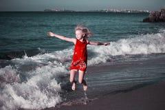 Gelukkig meisje die in gekleurde kleding op de golven op het strand springen royalty-vrije stock afbeelding