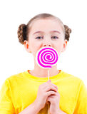 Gelukkig meisje die in gele t-shirt gekleurd suikergoed eten Royalty-vrije Stock Fotografie
