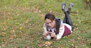 Gelukkig meisje die in het park op het gras liggen Foto's op telefoon Geel gebladerte stock videobeelden