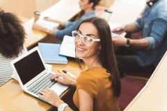 Gelukkig meisje die laptop met behulp van bij lezingszaal stock fotografie