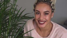 Gelukkig meisje die met mooie ogen dichtbij bladeren van installatie in ruimte glimlachen stock video