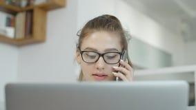 Gelukkig meisje die mobiele cel telefoon, het gebruiken van laptop thuis, het babbelen in sociale netwerken en het glimlachen spr stock video