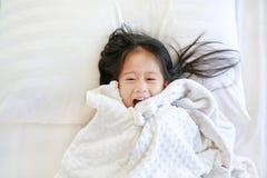 Gelukkig meisje die op bed met algemeen liggen en camera bekijken Hoogste mening stock foto