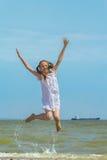 Gelukkig meisje die over het overzees springen stock afbeeldingen