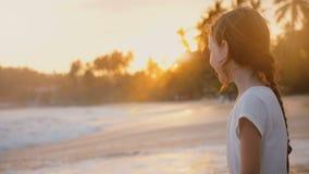 Gelukkig meisje die pret het genieten hebben van schuimend en bespattend overzeese golven die op haar benen op epische zonsonderg stock videobeelden