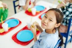 Gelukkig meisje die schoolmaaltijd eten royalty-vrije stock foto