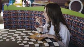 Gelukkig meisje die smakelijke gelei op een lijst in koffie eten 4K stock footage
