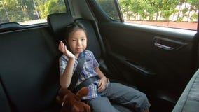 Gelukkig meisje die smartphone van de veiligheidsgordelsgreep in auto dragen stock footage