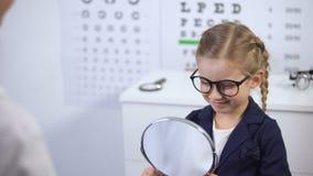 Gelukkig meisje die in spiegel kijken, die modieuze glazen met artsenhulp kiezen stock videobeelden