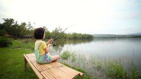 Gelukkig meisje die staaf trekken terwijl visserij tegen landschap van meer stock video