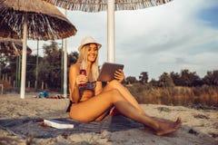 Gelukkig meisje die tablet op het strand gebruiken stock foto