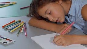 Gelukkig meisje die terwijl het trekken in haar sketchbook glimlachen stock footage