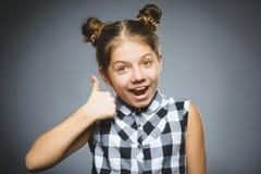 Gelukkig meisje die thubs verschijnen Het kind van het close-upportret glimlachen geïsoleerd op grijs royalty-vrije stock foto's