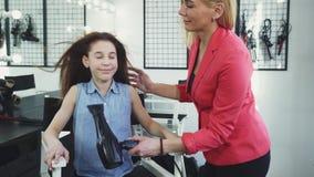 Gelukkig meisje die van haar haar genieten die droog door een kapper bij de salon zijn stock videobeelden