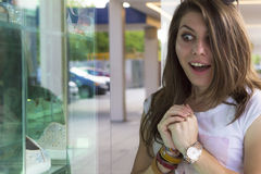 Gelukkig meisje die in winkelvenster kijken stock foto's