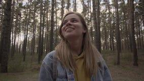 Gelukkig meisje die zich in het zonnige bos en de glimlach bevinden stock footage