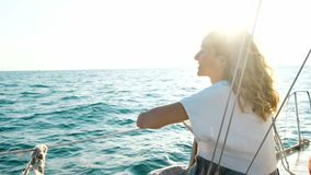 Gelukkig meisje in een kledingszitting op het dek en het onderzoeken van de open zee stock videobeelden