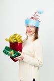 Gelukkig meisje in een ongebruikelijke Kerstmishoed met giftdozen Stock Afbeeldingen
