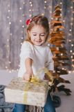 Gelukkig meisje in een witte sweater en jeans die dichtbij Kerstmisboom stellen Stock Foto