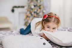 Gelukkig meisje in een witte sweater en jeans die dichtbij Kerstmisboom stellen Royalty-vrije Stock Foto