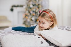 Gelukkig meisje in een witte sweater en jeans die dichtbij Kerstmisboom stellen Stock Foto's