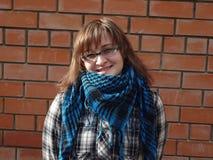 Gelukkig meisje in glazen en van de van het plaidjasje en sjaal verblijf over bric stock fotografie