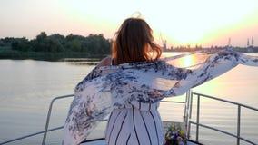 Gelukkig meisje in golvende kledij om status te winden op aan boord van jacht in overzees op achtergrond van zonsondergang hierbo stock videobeelden