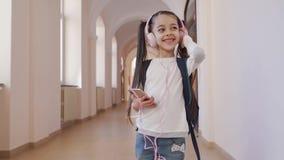 Gelukkig meisje in hoofdtelefoons en het luisteren muziek in school stock footage