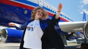 Gelukkig meisje in luchthaven eenvormige dansen tegen vliegtuig stock video