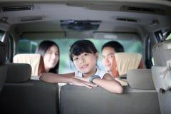 Gelukkig meisje met Aziatische familiezitting in de auto voor enjo Stock Foto's