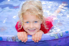 Gelukkig meisje met blauwe ogen in een pool. stock foto