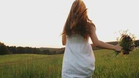 Gelukkig meisje met bloemboeket die op gebied bij zonsondergang lopen, die in weide in zonstralen genieten van, het glimlachen stock videobeelden