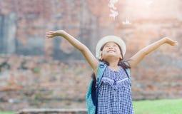 Gelukkig meisje met de bloem van het rugzakspel stock fotografie