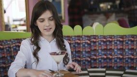Gelukkig meisje met de cocktailgelei van glimlachrotaties op een lijst in koffie 4K stock video