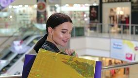Gelukkig meisje met document zakken in de wandelgalerij op de achtergrond van de roltrap stock video