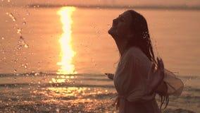 Gelukkig meisje met donker haar die bespattende handen doen die zich in de rivier tegen de zon tijdens zonsondergang bevinden Lan stock videobeelden