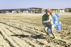 Gelukkig meisje met een opblaasbare cirkel die langs het strand lopen Stock Afbeeldingen