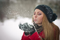 Gelukkig meisje met GLB en handschoenen die met sneeuw spelen Stock Afbeeldingen