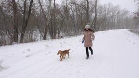 Gelukkig meisje met haar favoriete die hond die en in blizzard in werking wordt gesteld lachen Langzame Motie stock videobeelden