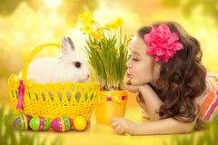 Gelukkig meisje met het konijn en de eieren van Pasen Stock Afbeeldingen