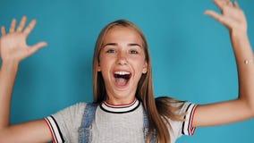 Gelukkig meisje met lang haar die en handen houden bij haar gezicht lachen terwijl status binnen binnen van geïsoleerd over blauw stock footage
