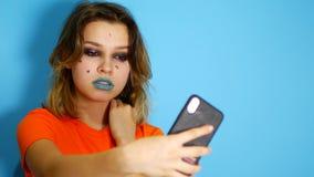 Gelukkig meisje met lang haar die en handen houden bij haar gezicht lachen terwijl status binnen binnen van geïsoleerd over blauw stock video