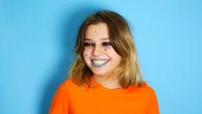 Gelukkig meisje met lang haar die en handen houden bij haar gezicht lachen terwijl status binnen binnen van geïsoleerd over blauw stock videobeelden