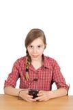 Gelukkig Meisje met Oortelefoons die bij de Lijst zitten binnen en aan Muziek op Haar die Cellphone luisteren op Wit wordt geïsol Stock Foto